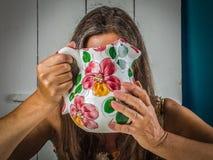 Женщины среднего возраста спрятанные за кувшином молока стоковые изображения rf