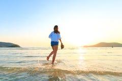 Женщины стоят и держат шляпа на пляже между заходом солнца Стоковые Изображения RF