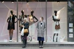 2 женщины стоят на окне магазина, ждать друзей Стоковая Фотография