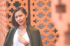Женщины стоят против кирпичной стены стоковая фотография