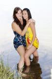 2 женщины стоя в воде с платьями Стоковые Фотографии RF
