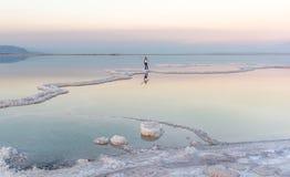 Женщины стоя в мертвом море на заходе солнца Стоковое Изображение RF