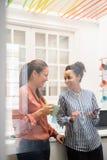 2 женщины стоя и смеясь над в кухне Стоковые Фото