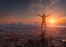 Женщины стоя на скале к городскому пейзажу и устанавливая su Стоковая Фотография