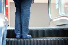 Женщины стоя на эскалаторе на моле Стоковые Изображения