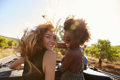 2 женщины стоя позади открытого автомобиля поворачивая к камере Стоковые Фотографии RF