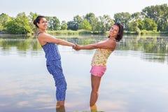 2 женщины стоя совместно в воде Стоковые Изображения