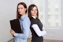2 женщины стоя спина к спине против окна Стоковое Изображение RF