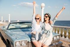 2 женщины стоя с поднятыми руками приближают к винтажному cabriolet Стоковые Изображения RF