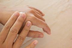 Женщины сушат руки, прикладывают заботу кожи или лосьон Стоковое Фото