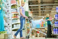 Женщина покупкы с тележкой на супермаркете стоковые фотографии rf