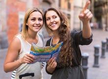 2 женщины с багажем проверяя трассу outdoors Стоковые Фото