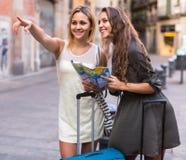 2 женщины с багажем проверяя трассу outdoors Стоковые Изображения