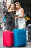 2 женщины с багажем проверяя трассу outdoors Стоковое Изображение