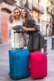 2 женщины с багажем проверяя трассу outdoors Стоковое Фото
