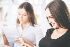 Женщины с блокнотом и smartphone Стоковая Фотография RF