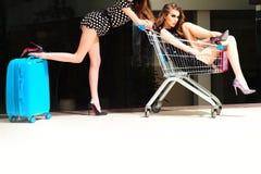 2 женщины с вагонеткой покупок и голубой сумкой Стоковая Фотография RF