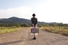 Женщины с винтажным чемоданом перемещения на старой дороге Фото в изображении s Стоковые Фото