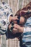 2 женщины с лежать солнечных очков усмехаясь в одеяле Стоковые Изображения RF