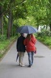 Женщины с зонтиком идут для пути вперед Стоковое Изображение