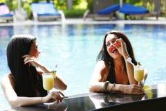 2 женщины с коктеилами в плавательном бассеине Стоковые Изображения
