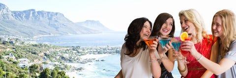 Женщины с коктеилями против расплывчатой береговой линии Стоковые Фотографии RF