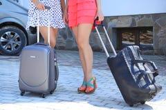 2 женщины с крупным планом чемодана уменьшают ноги Стоковые Фото