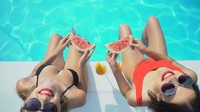 2 женщины с кусками арбуза играя с водой и смотря камеру, гостиницу сток-видео