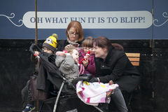 2 женщины с малыми детьми сидят на стенде около Ковент Гардена Стоковые Фото