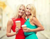 Женщины с на вынос кофейными чашками в городе Стоковое Фото