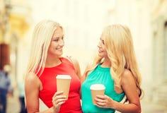 2 женщины с на вынос кофейными чашками в городе Стоковые Изображения
