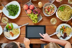 Женщины с ПК таблетки на таблице вполне еды Стоковое Фото