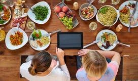 Женщины с ПК таблетки на таблице вполне еды Стоковое фото RF