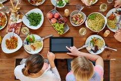 Женщины с ПК таблетки на таблице вполне еды Стоковые Фото