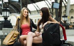 Женщины с поездом багажа ждать на станции стоковые фотографии rf