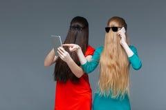 2 женщины с покрытыми сторонами используя мобильный телефон и таблетку Стоковые Фото