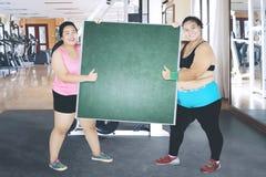 2 женщины с пустой доской в центре спортзала Стоковое фото RF