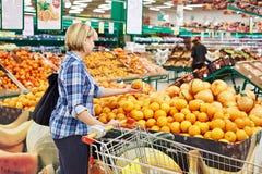 Женщины с плодоовощ покупок тележки оранжевым Стоковое фото RF