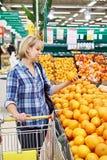 Женщины с плодоовощ покупок тележки оранжевым Стоковые Изображения RF