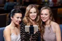 Женщины с ручкой selfie smartphone на ночном клубе стоковые фото