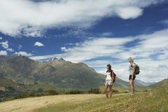 2 женщины с рюкзаками на ландшафте горы Стоковое фото RF