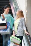 Женщины с сумками на moving лестнице Стоковое Изображение RF