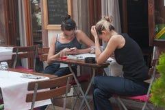 2 женщины с умным телефоном в террасе ресторана Стоковое фото RF