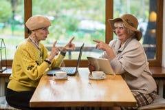 Женщины с устройствами на таблице Стоковые Фото
