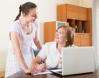 Женщины с финансовыми документами и компьтер-книжка на таблице Стоковое Фото