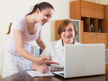 Женщины с финансовыми документами и компьтер-книжка на таблице Стоковое Изображение