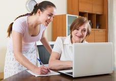 Женщины с финансовыми документами и компьтер-книжка на таблице Стоковая Фотография RF