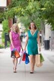 Женщины с хозяйственными сумками на тротуаре Стоковые Изображения