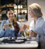 2 женщины с чаем и шоколадами в кафе Стоковое Изображение