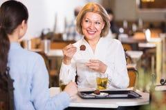 2 женщины с чаем и шоколадами Стоковые Изображения RF